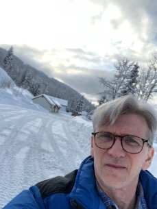 Image may contain: 1 person, eyeglasses, sky, snow, cloud, mountain, tree, outdoor and nature