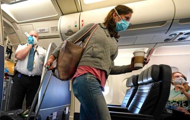 a person sitting in a car: Canadians will encounter new rules when flying. They must wear face masks when in transit and at most major Canadian airports.